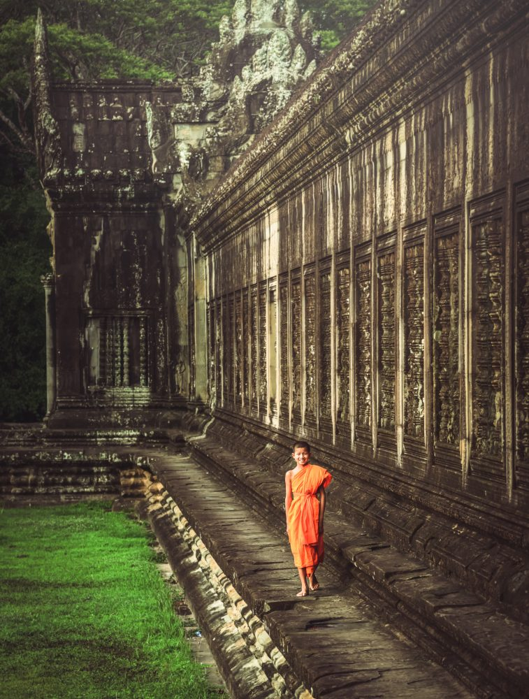 A young monk stands in Angkor Wat temple, marathon – Shutterstock